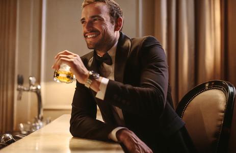 Smiling man having a drink at night club