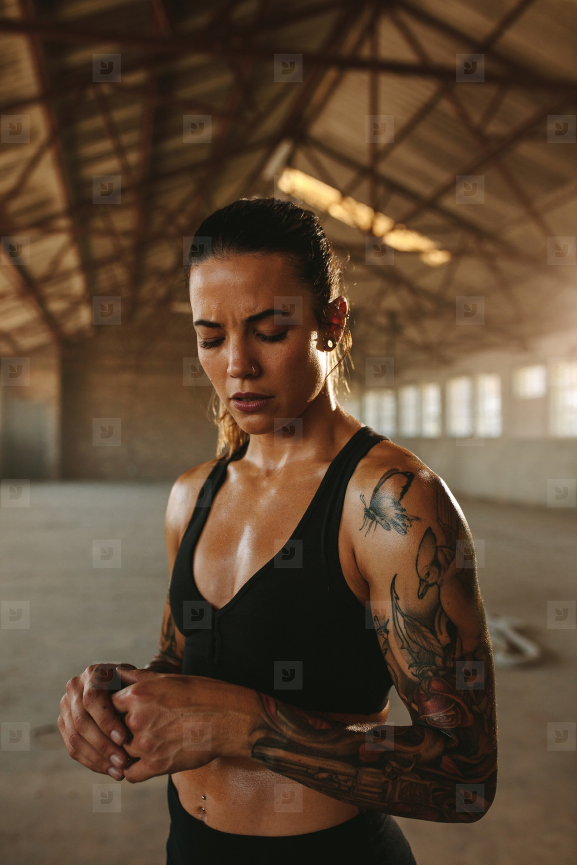 Muscular woman inside abandoned warehouse