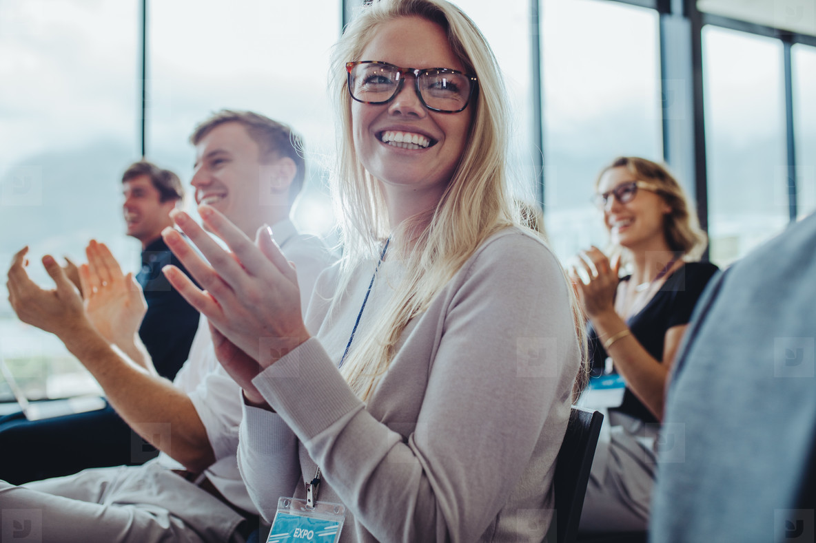 Businesspeople sitting at seminar clapping hands