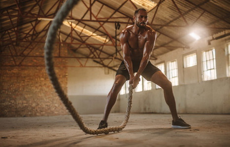 Strong and masculine athlete working out with battle rope