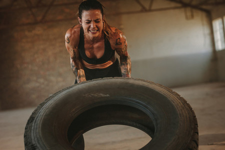 Tough woman doing tire flip workout