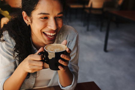 Woman having coffee and smiling in a cafe