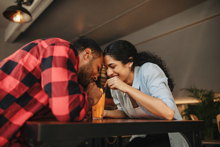 Loving couple having juice from same glass