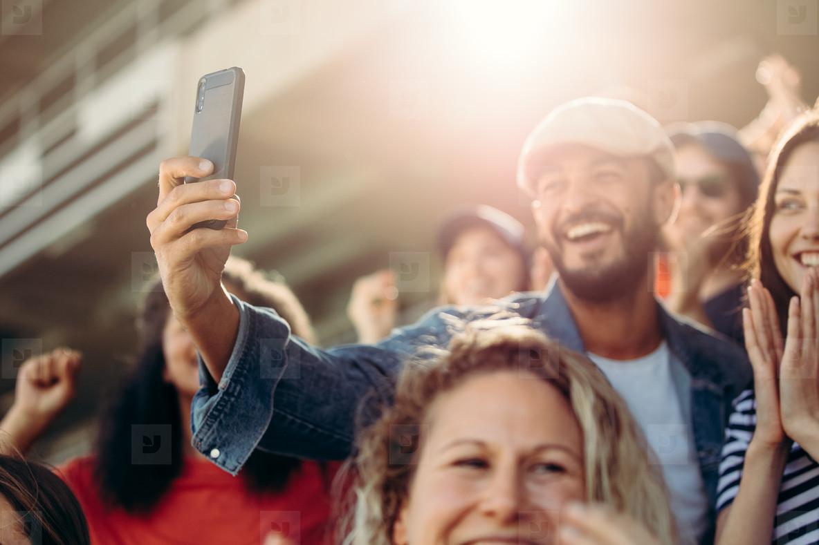Excited couple taking selfie at stadium