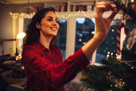 Woman happily decorating Christmas tree