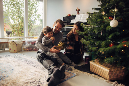 Parents giving Christmas gifts to their son