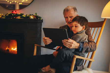 Grandfather and grandson using a digital tablet