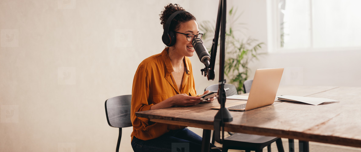 Woman recording a podcast from home studio