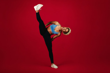 Fitness woman working out on maroon background