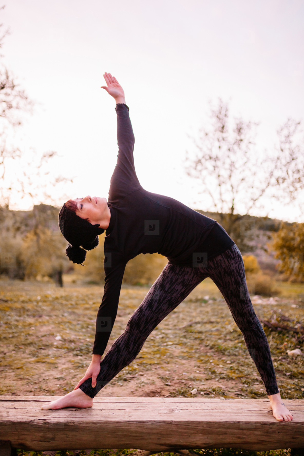 Woman practicing yoga and stretching on the park bench