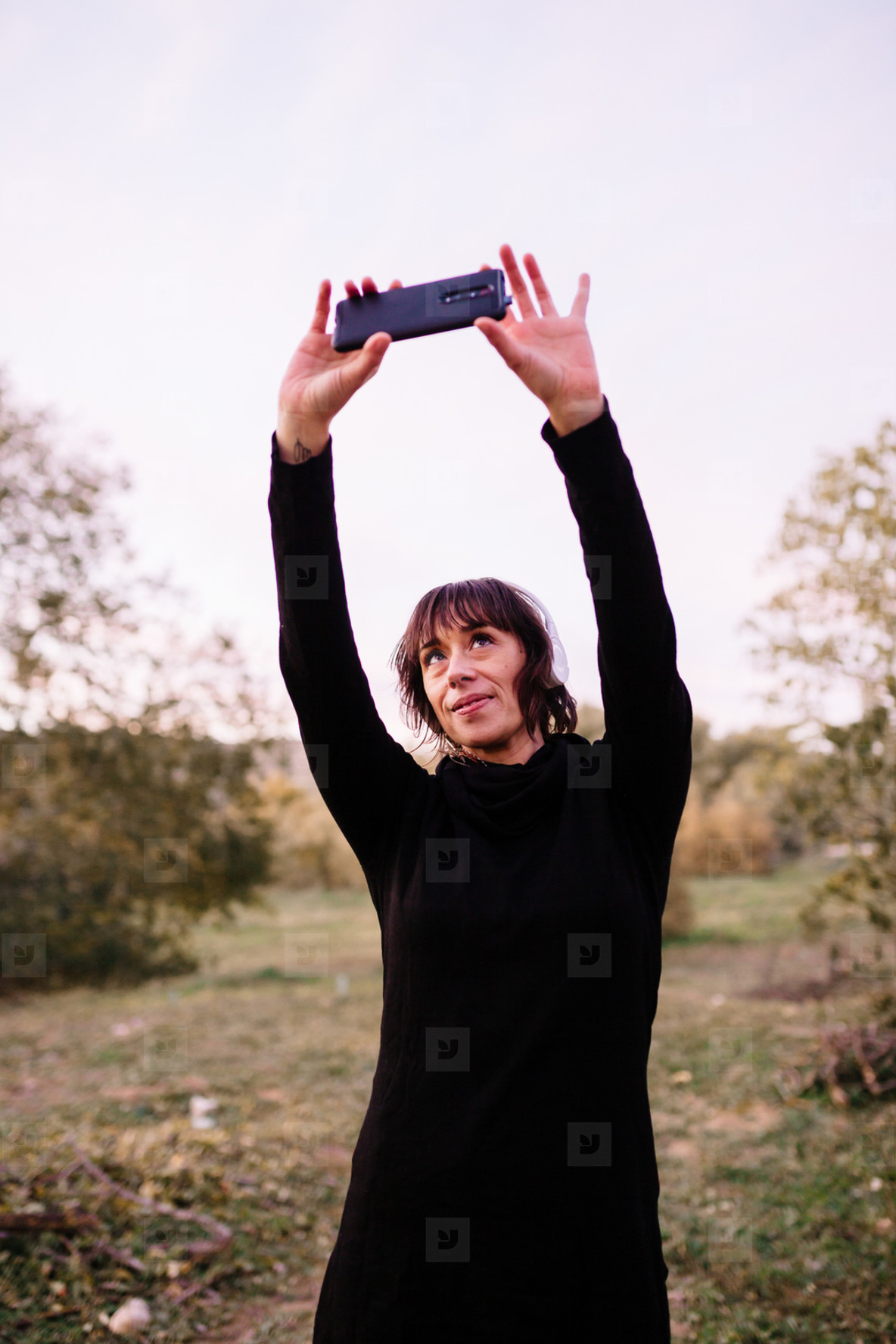 Woman in sport clothes on a wooden bench taking a selfie