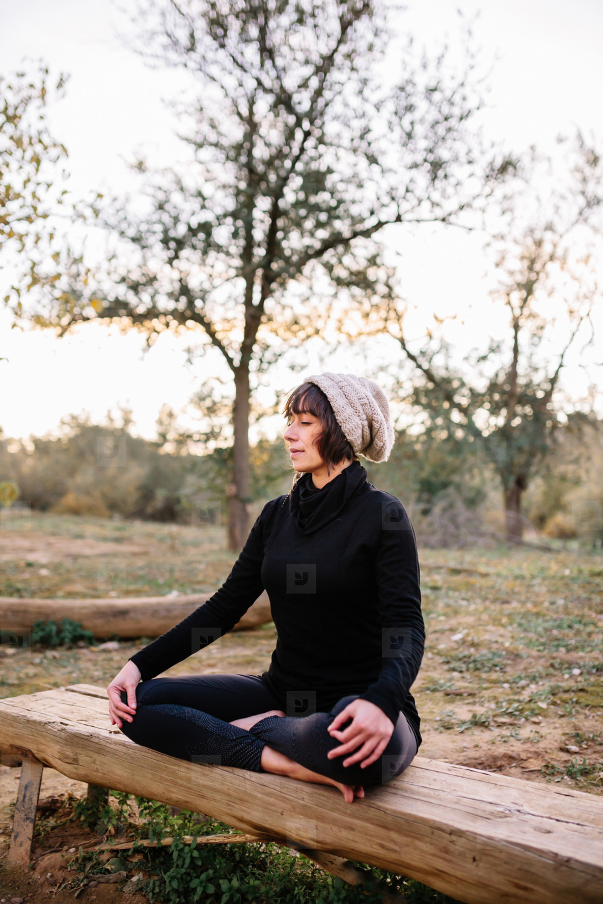 Woman practicing yoga and meditating on the park bench
