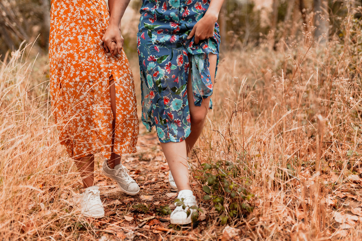 Two young lesbians walking in the woods wearing long dresses