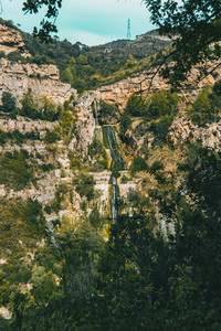 Landscape wit views of a waterfall flowing through the slope of a steep mountain