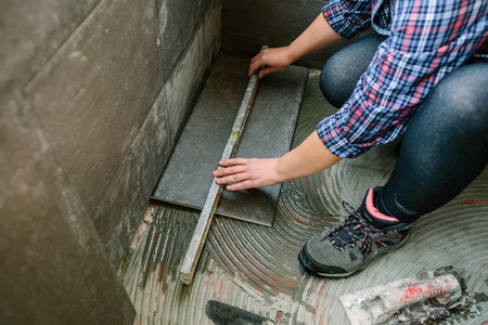 Female bricklayer checking floor with a level