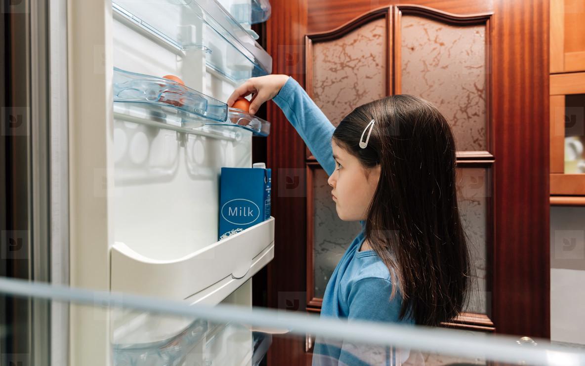 Sad girl taking an egg from the empty fridge