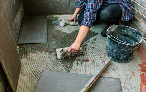 Female mason laying tiles on a terrace