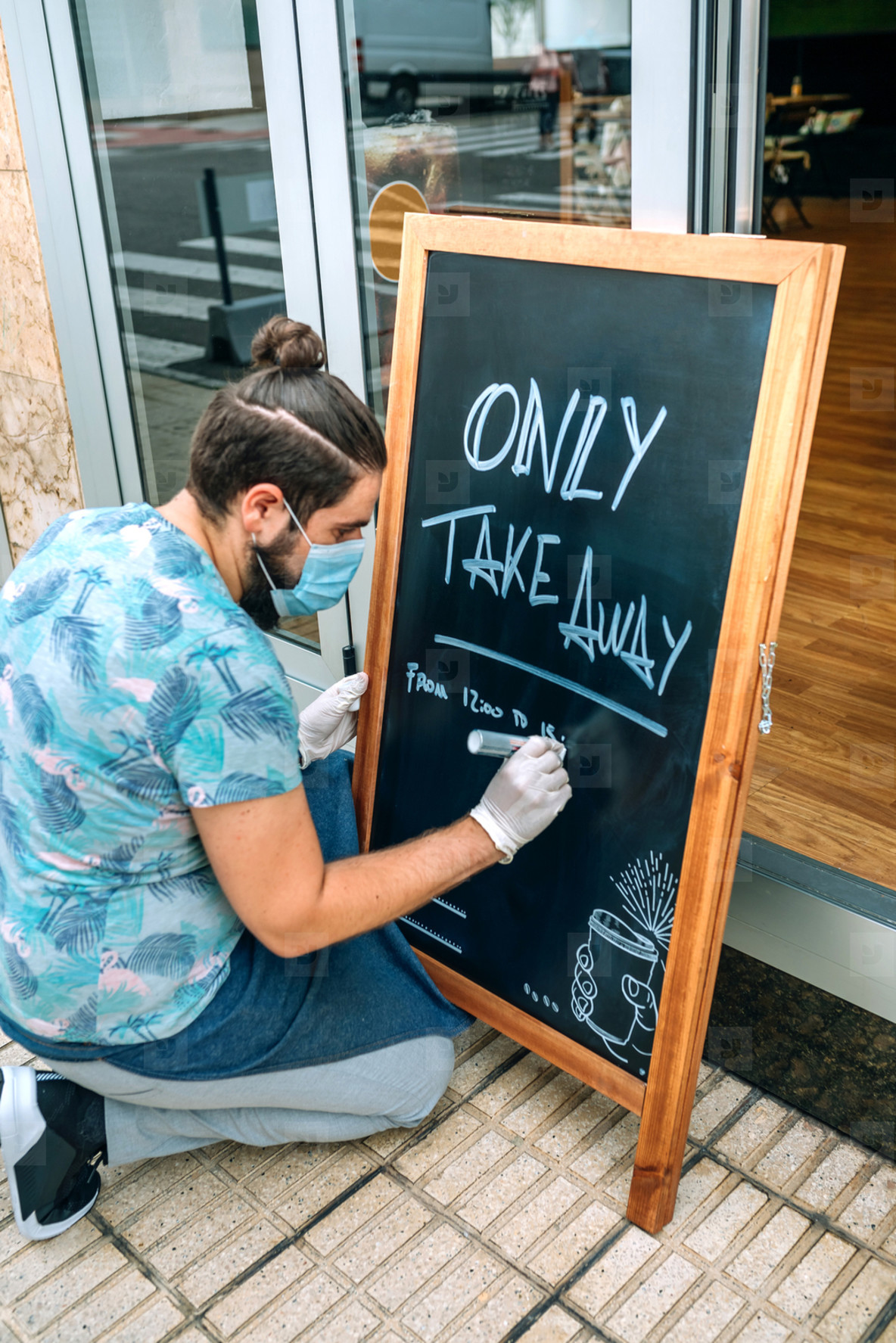Restaurant owner writing on a blackboard