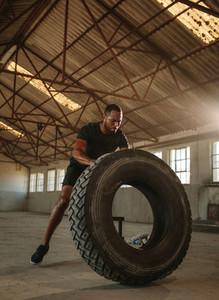 Masculine man doing tire flip workout