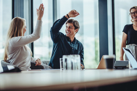 Business colleagues giving a high five in meeting room