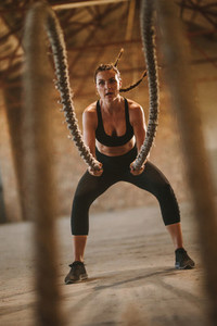 Fitness woman exercising with battle rope