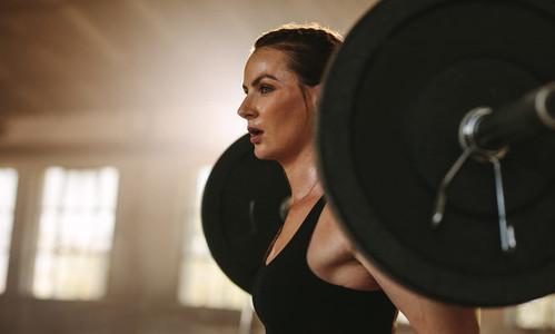 Woman exercising back squats with a barbell