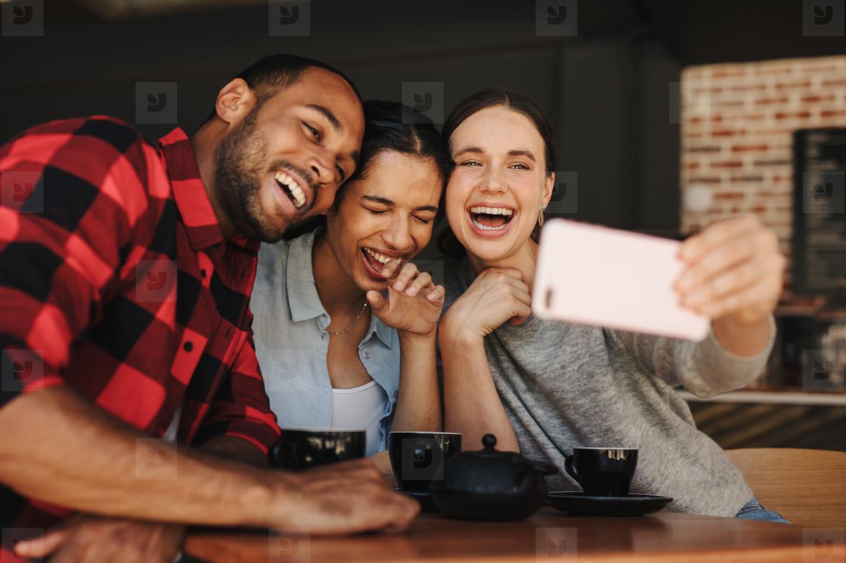 Friends in coffee shop having fun and taking selfies