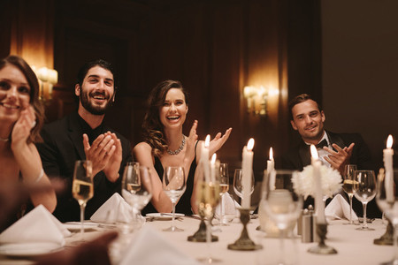 High society people clapping hands at dinner party