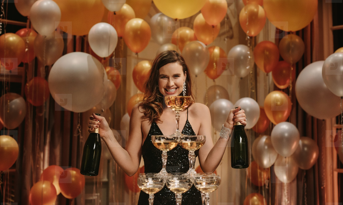 Smiling woman with pyramid of champagne