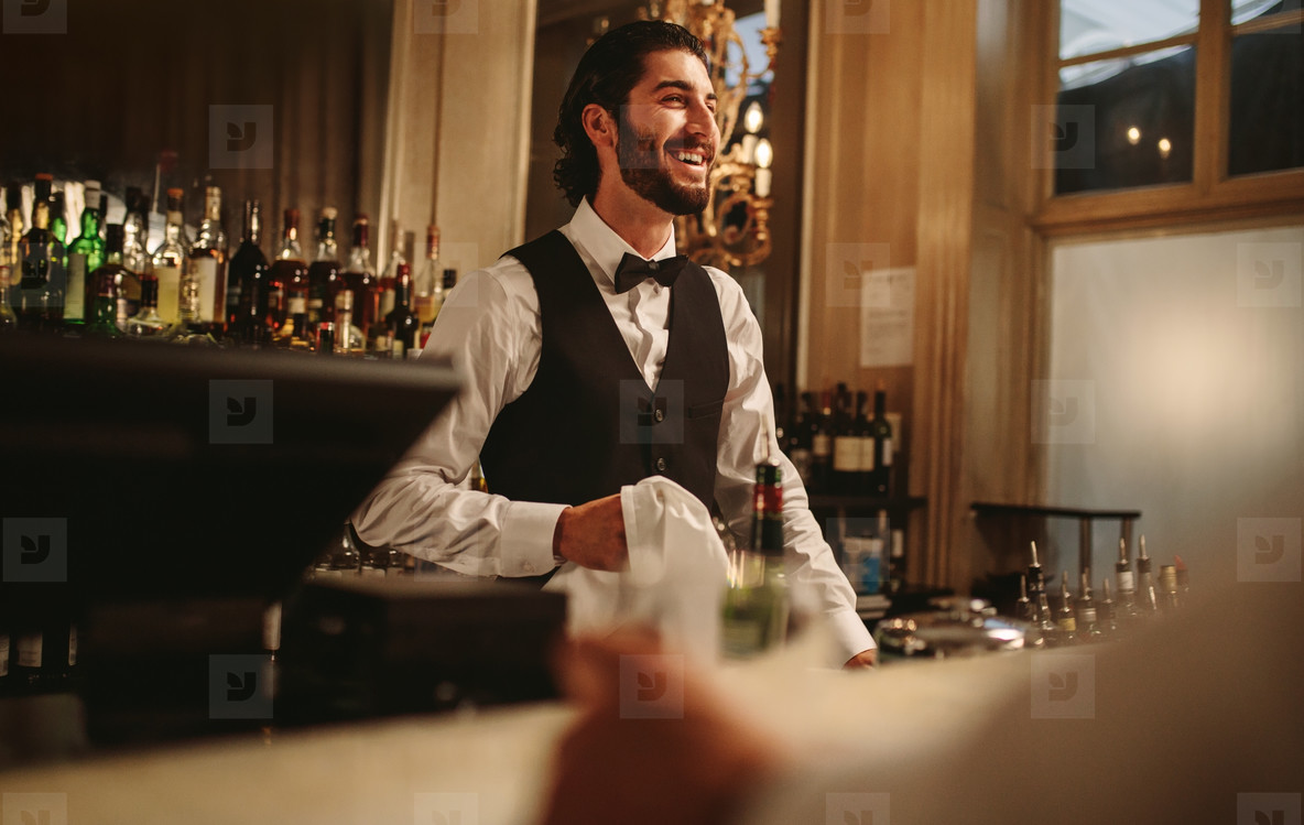 Smiling barman standing behind the counter