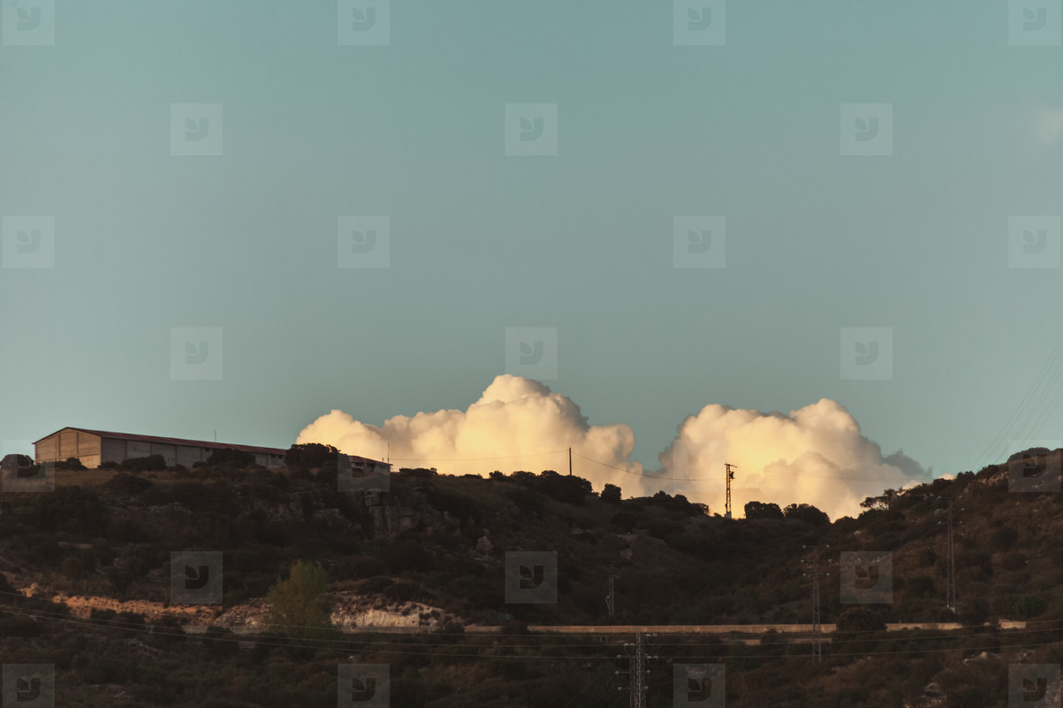 Sunset scene with clouds behind hills