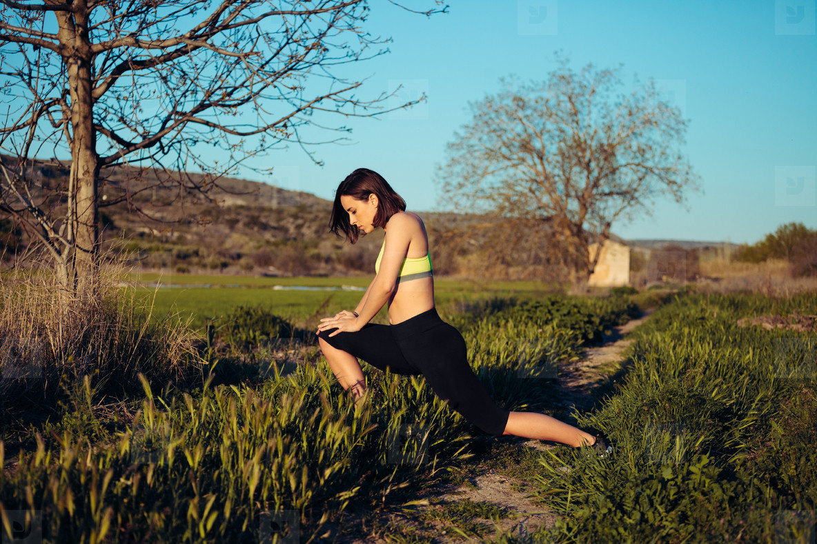 Female runner stretching outdoors in the field before exercise