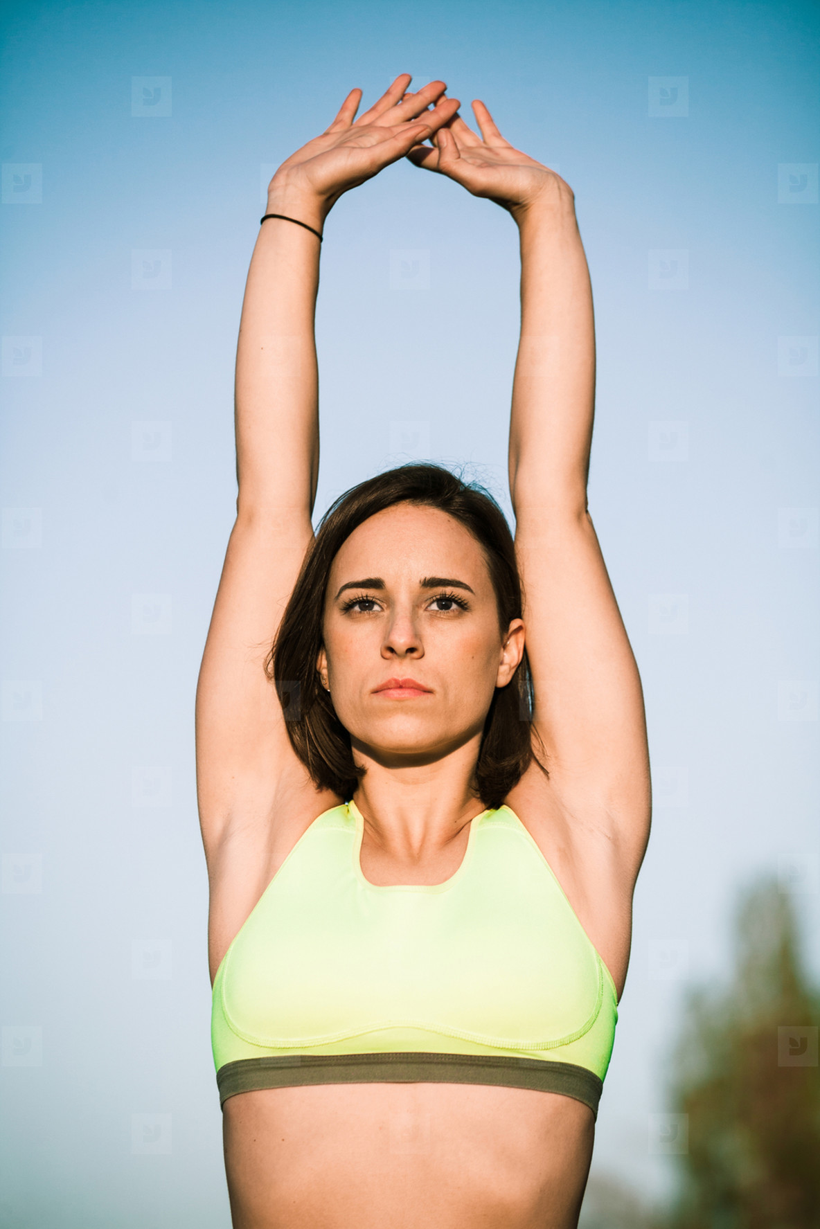 Brunette woman in sportswear doing stretching exercise with arms up while working out