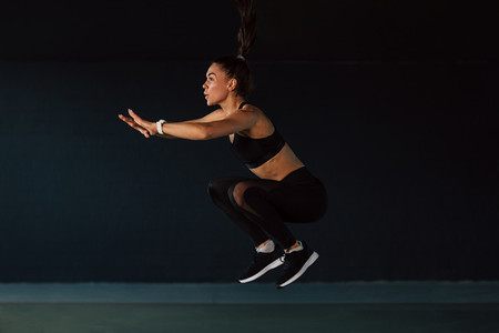 Side view of female athlete jump
