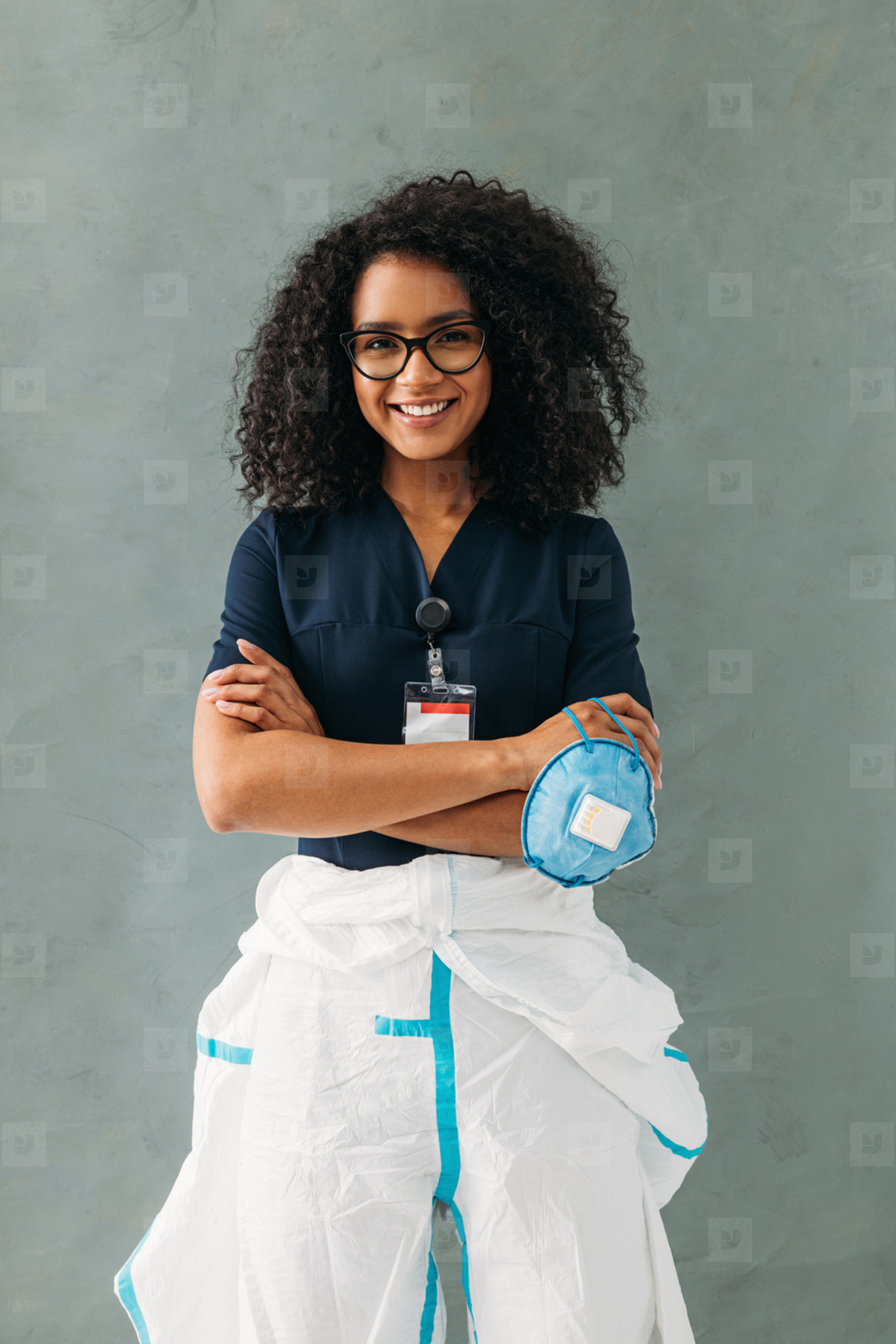 Smiling nurse standing at wall