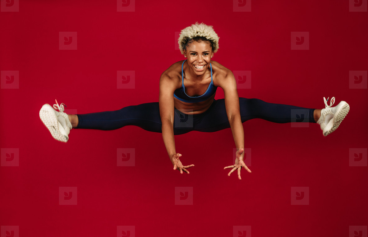 Smiling female athlete stretching her legs in air