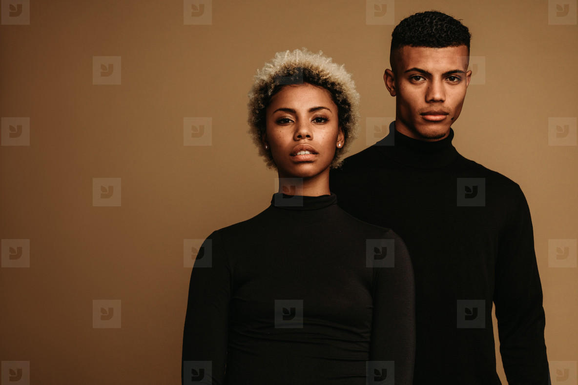 African american couple standing together on brown background