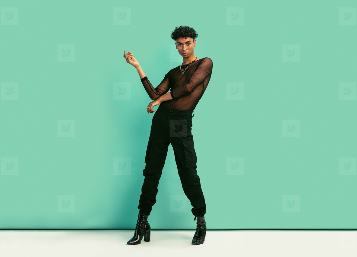 Gender fluid man with womens clothing posing at studio