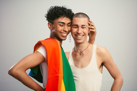 Cheerful gay couple with pride flag