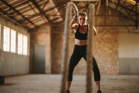 Strong woman working out with battle rope