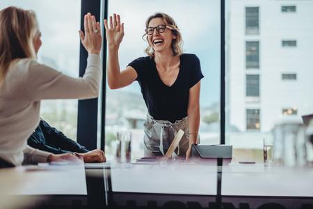 Businesswomen high five in a board room meeting
