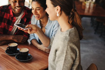 Woman taking pictures of coffee with friends