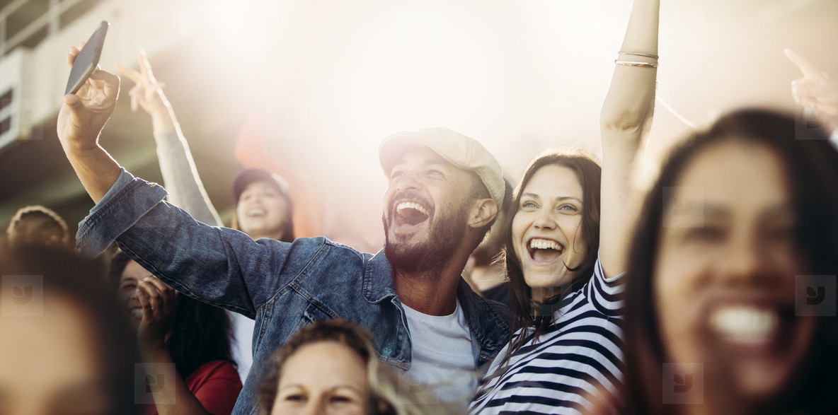 Couple taking selfie while watching a match at stadium