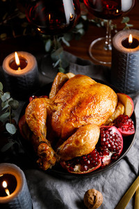 Whole roast chicken with pomegranate  apple and red wine on a festive table  Christmas or New Year cooking concept