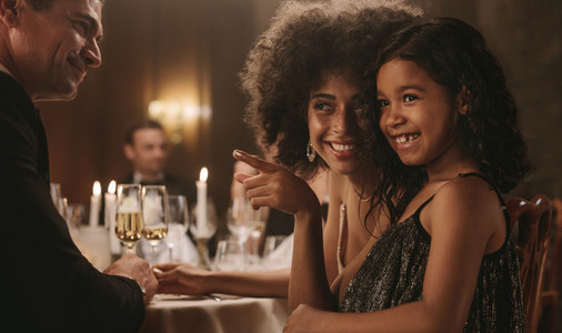 Mother and daughter at a dinner party with friends