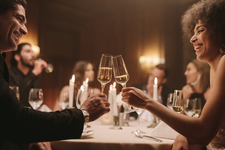 Cheerful friends having drinks at dinner party
