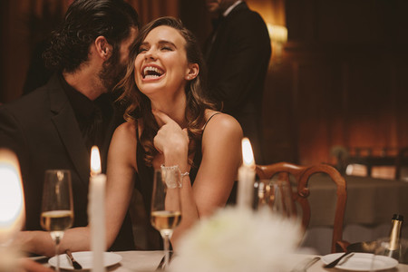 Cheerful couple enjoying at gala dinner
