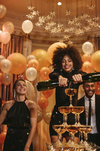 Woman filling pyramid of champagne at new years eve