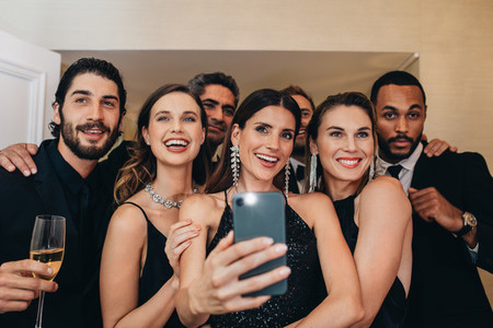 Multi ethnic group of people taking a selfie at a party