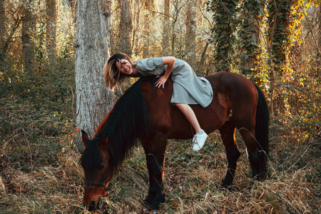 Beautiful young woman hugging brown horse and wearing dress